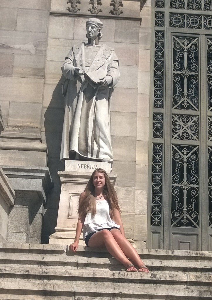 """Photo shows me sitting on the steps under a large statue of a robed figure with the word """"Nebrija"""" inscribed below."""